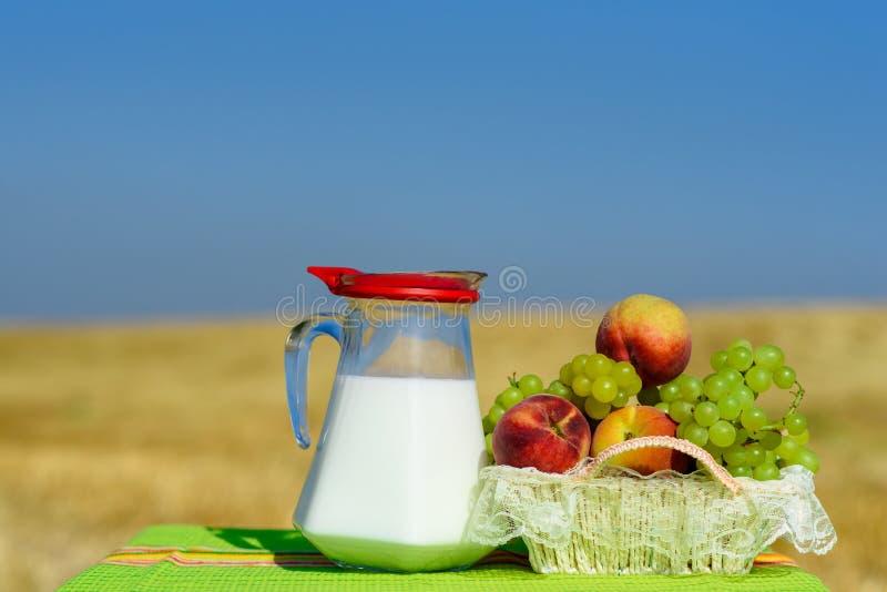 葡萄和桃子在秸杆白色篮子室外在黄色麦田背景 免版税库存图片