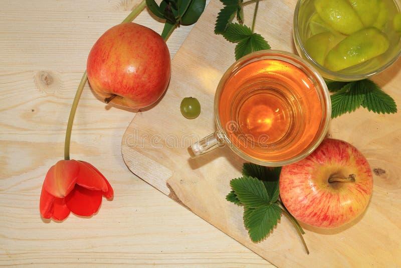 葡萄和苹果汁、苹果和梨在木背景,春天郁金香,顶视图 免版税库存图片