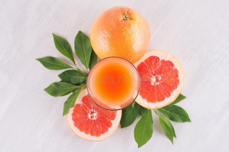 葡萄柚夏天明亮的新鲜的桃红色鸡尾酒与绿色叶子的,在白色木背景,顶视图的切片葡萄柚 库存照片