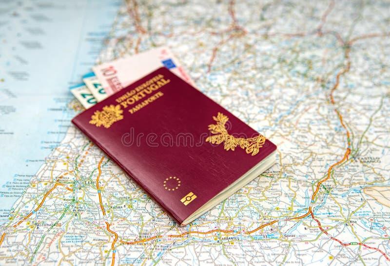 葡萄牙护照和欧洲钞票在一张地理地图 免版税库存照片