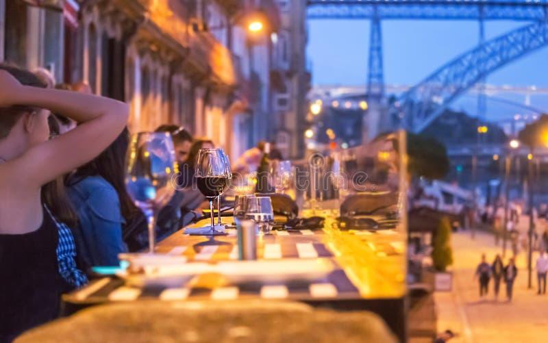 葡萄牙波尔图 — 2019年5月2日:人们享用葡萄酒、夜晚和路易斯一桥(金属桥 — 象征波尔图)的景色 图库摄影