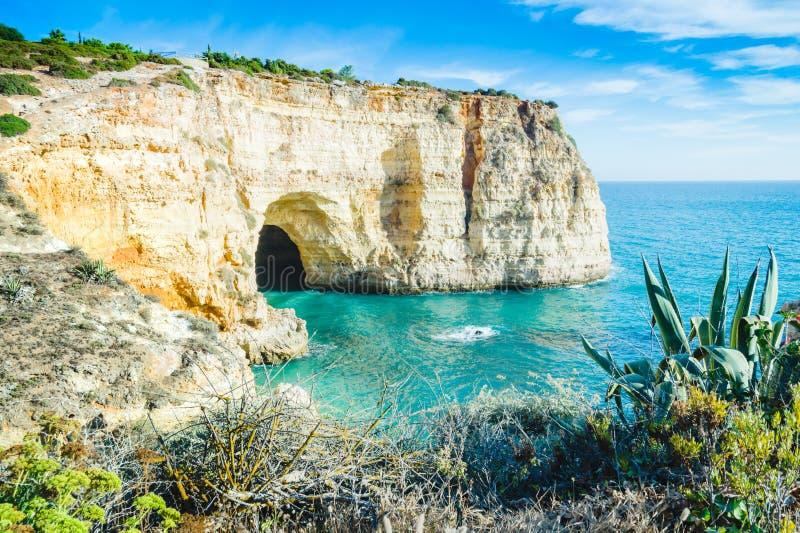 葡萄牙阿尔加威海滩与地方共同的植被的洞视图 免版税库存图片