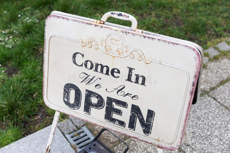 葡萄酒与'进来我们文本词的标志板是开放的' 免版税库存图片