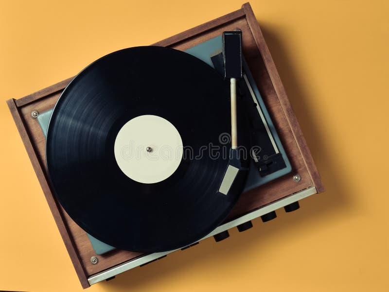 葡萄酒与乙烯基板材的乙烯基转盘在黄色淡色背景 听音乐 顶视图 库存照片