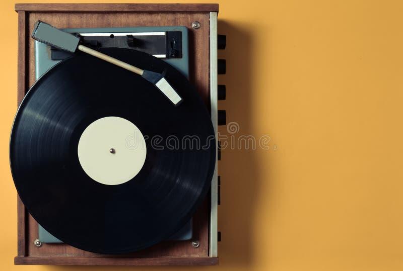 葡萄酒与乙烯基板材的乙烯基转盘在黄色淡色背景 娱乐70s 听音乐 免版税库存图片