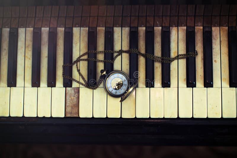 """葡萄酒与古色古香的怀表的钢琴钥匙有链â€的""""计时概念 免版税库存照片"""