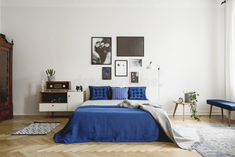 葡萄酒与床头柜的卧室内部,与蓝色卧具的加长型的床和枕头 在白色墙壁上的大模型画廊 图库摄影