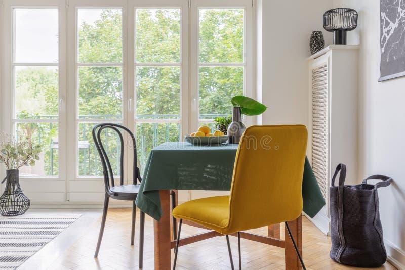 葡萄酒与桌、黄色椅子和大阳台窗口的餐厅内部 免版税库存照片