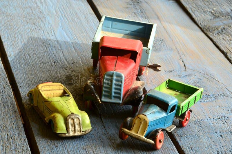 葡萄酒交换(卡车)玩具和covertible玩具汽车在蓝色木背景 免版税库存图片
