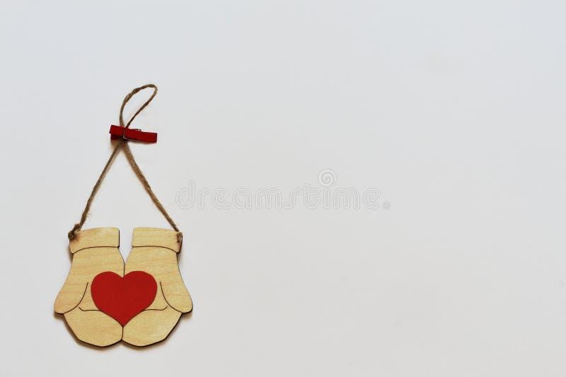 葡萄酒传统化了有心脏的木手套在与晒衣夹的黄麻绳子在白色背景 简单派样式 免版税库存照片