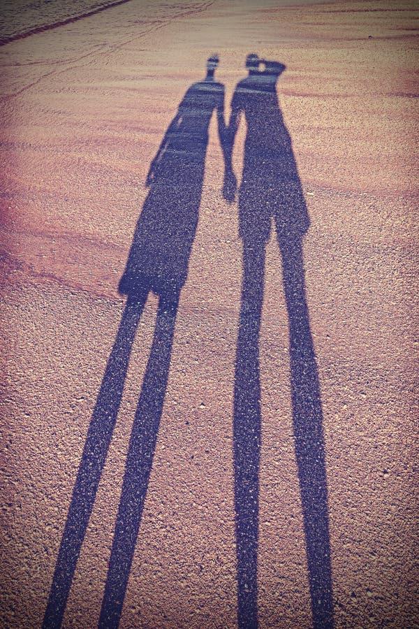 葡萄酒传统化了夫妇的阴影的图片在海滩的 免版税库存图片