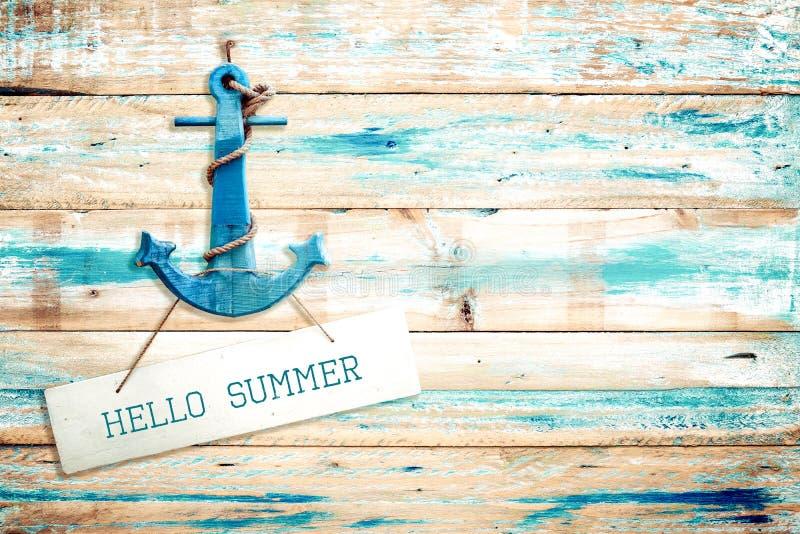 葡萄酒你好垂悬与在老木蓝色油漆背景的船锚的夏天标志 库存图片