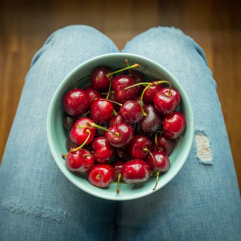 葡萄酒充分浅兰的碗的神色图象在穿牛仔裤的妇女的腿的红色樱桃 库存图片