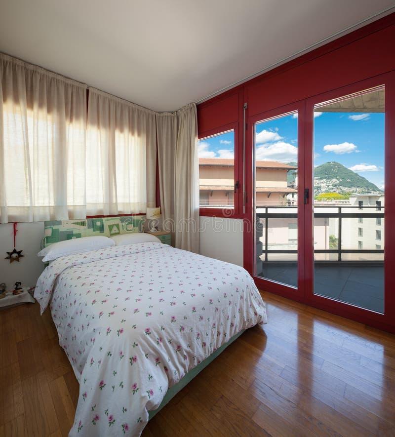 葡萄酒公寓主卧室与木条地板的 库存图片
