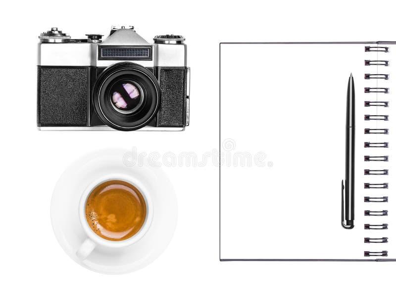 葡萄酒减速火箭的照片照相机、咖啡杯、在白色背景隔绝的笔记薄和笔 平的位置 库存图片