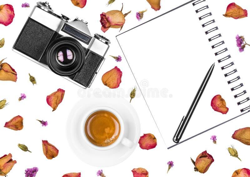 葡萄酒减速火箭的照片照相机、笔记薄、笔、在白色背景和干花隔绝的咖啡杯 平的位置 免版税库存图片