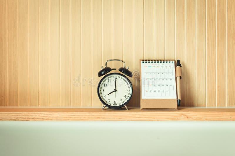 葡萄酒减速火箭闹钟和日历在床头板架子、内部卧室和装饰设计 黑定时器时钟是布局 免版税库存照片