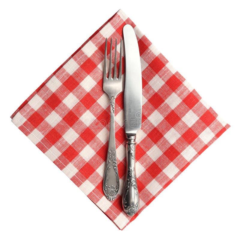 葡萄酒刀子和叉子在红色被隔绝的格子花呢披肩亚麻布餐巾 免版税库存图片