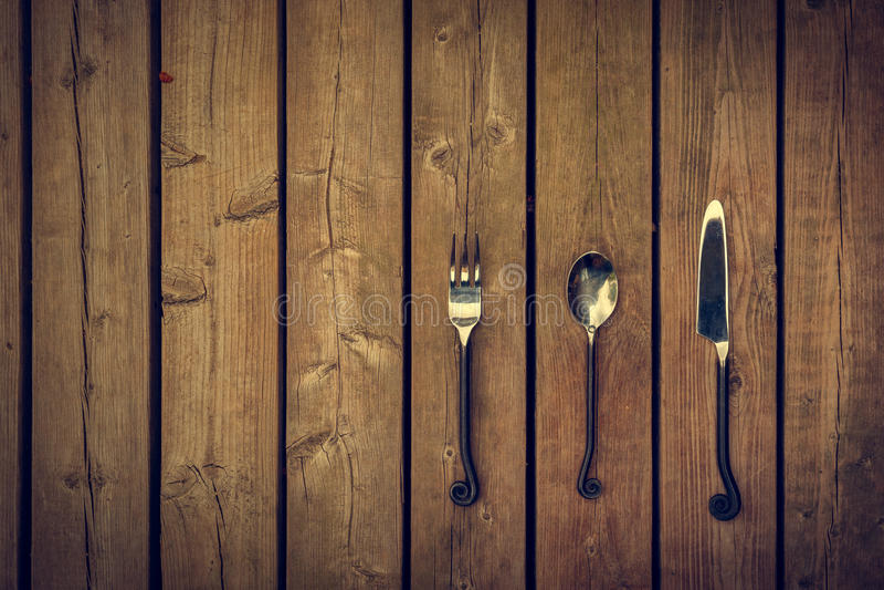葡萄酒利器-叉子、匙子和刀子在木背景 库存照片
