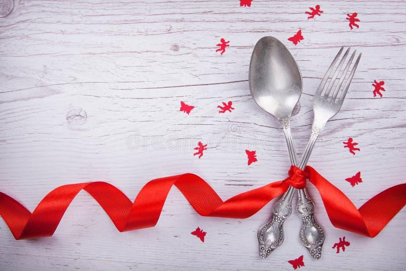 葡萄酒匙子和叉子与一繁文缛节,天使和蝴蝶为华伦泰` s天在木 库存图片