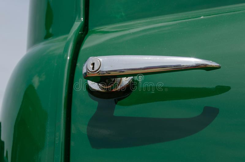 葡萄酒卡车在一个绿色门的门把手 免版税库存图片