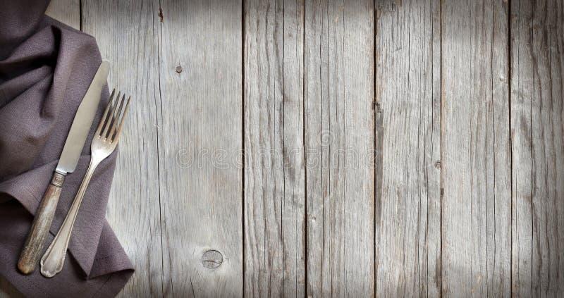 葡萄酒叉子和刀子在木头 免版税库存照片