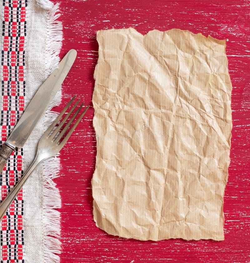 葡萄酒叉子和刀子在餐巾在红色木头和工艺纸 免版税库存照片