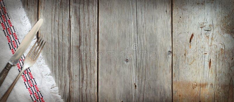 葡萄酒叉子和刀子在餐巾在老木头 免版税库存图片