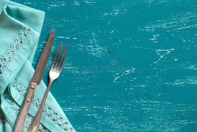 葡萄酒叉子和刀子在餐巾在绿松石木头 库存照片