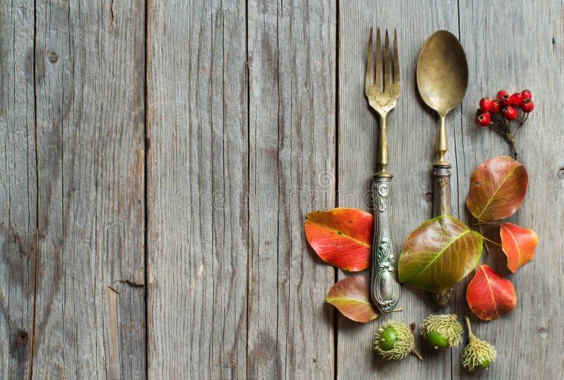 葡萄酒叉子和刀子有秋叶的在木头 免版税库存照片