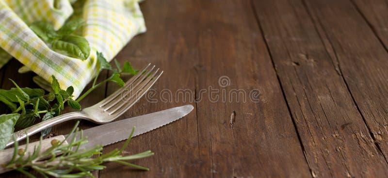 葡萄酒叉子和刀子用草本和餐巾 免版税库存图片