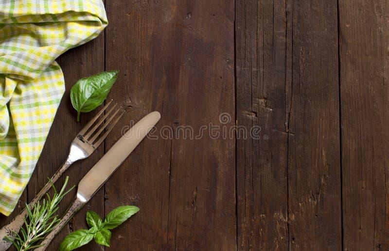 葡萄酒叉子和刀子用草本在一块五颜六色的餐巾 库存图片