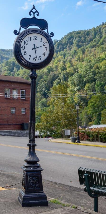 葡萄酒反对绿色山和绿色天空背景的街道时钟  库存图片