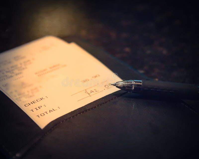 葡萄酒口气与餐馆票据检查和笔的皮革持有人 免版税库存图片