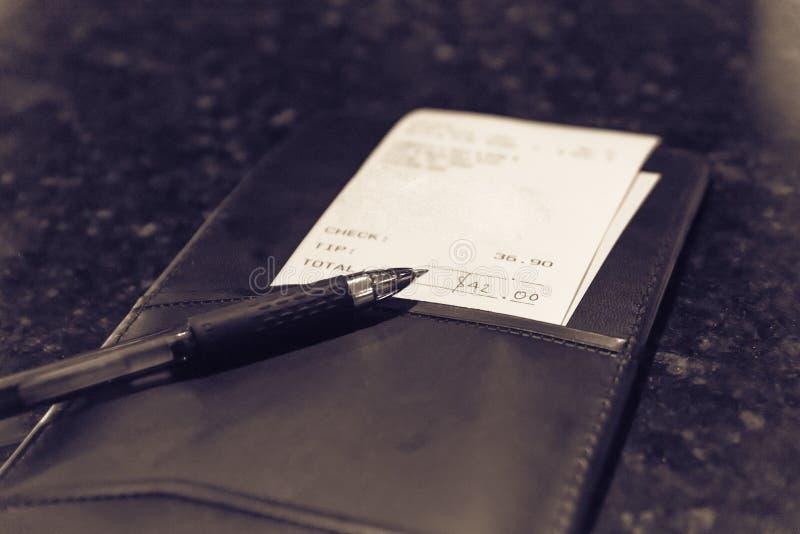 葡萄酒口气与餐馆票据检查和笔的皮革持有人 免版税库存照片