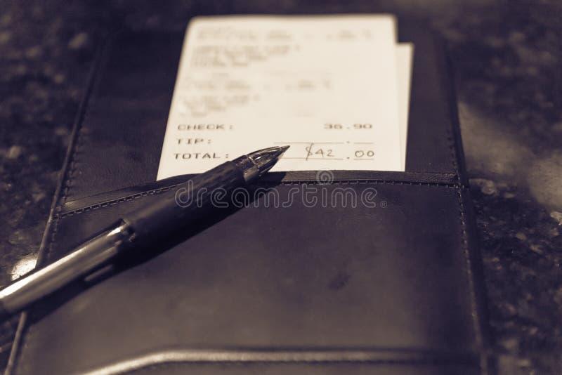 葡萄酒口气与餐馆票据检查和笔的皮革持有人 库存照片