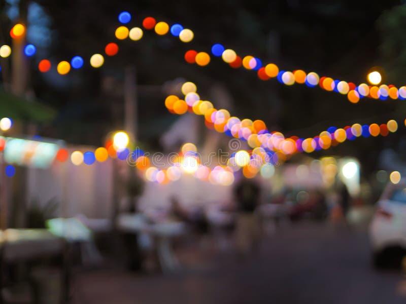 葡萄酒口气五颜六色夜节日的轻的抽象模糊的照片在街道上的有背景用法的轻的bokeh的 免版税库存图片