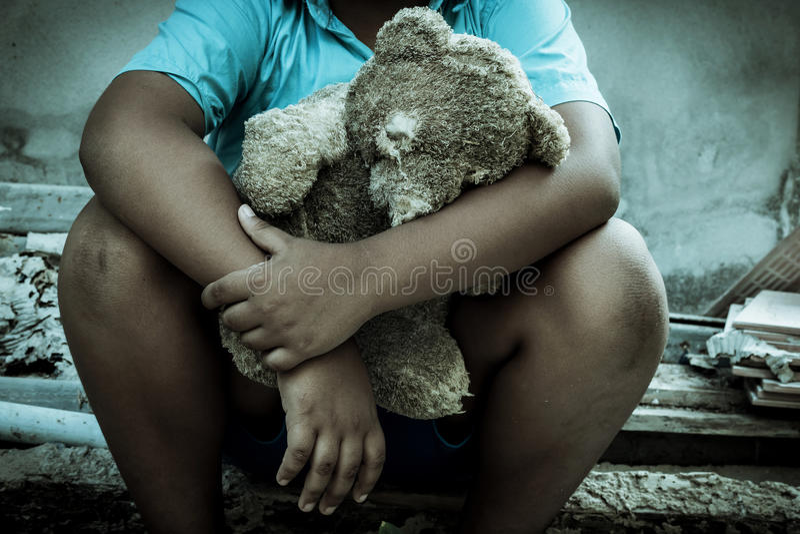葡萄酒口气,单独坐与玩具熊的哀伤的男孩 库存图片