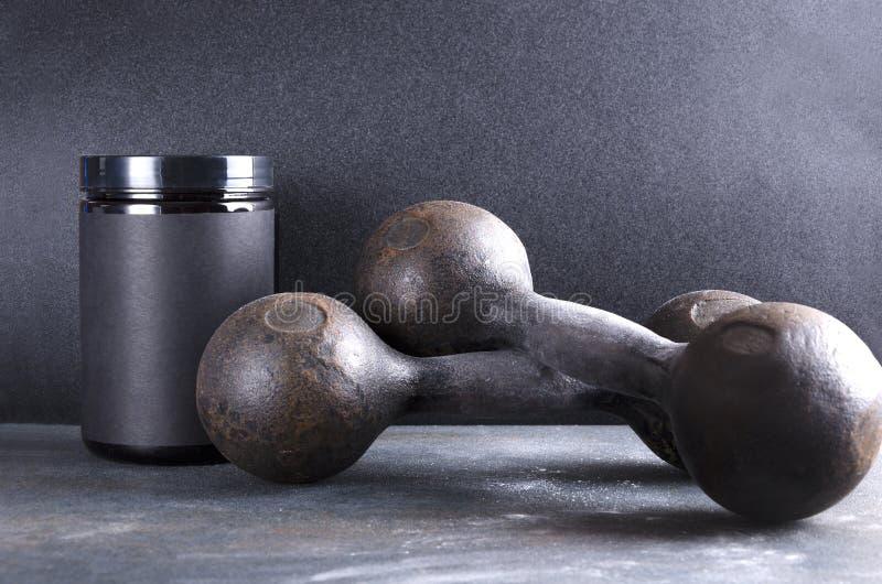葡萄酒哑铃和塑料罐头有体育营养的灰色表面上对黑暗的墙壁 免版税库存图片