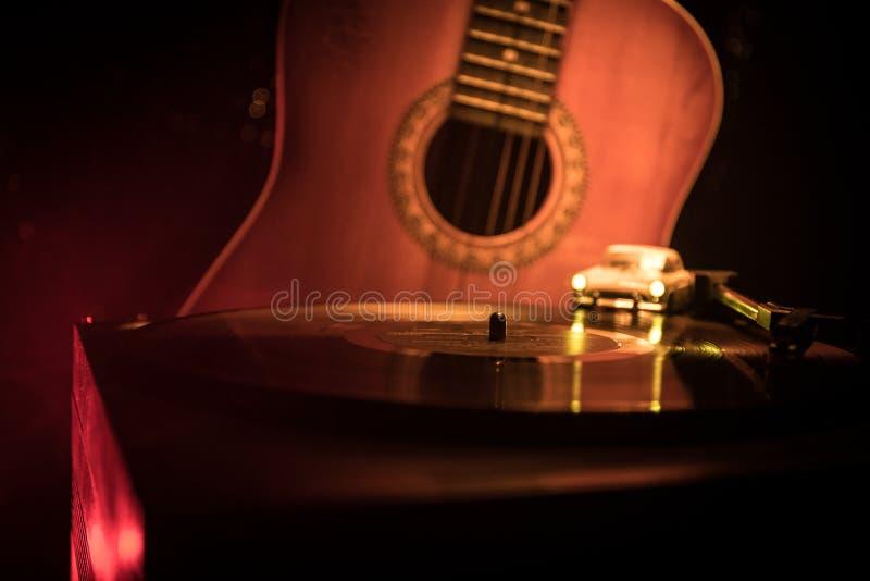 葡萄酒唱片使用在球员的和在背景的声学吉他用火桔子抽烟 蓝色概念 使用玩具汽车 库存图片