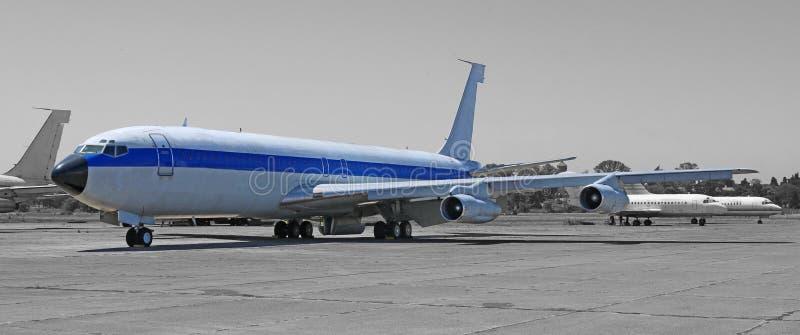 葡萄酒商业飞机,在机场平台的军用飞机 退休的飞机 免版税库存照片