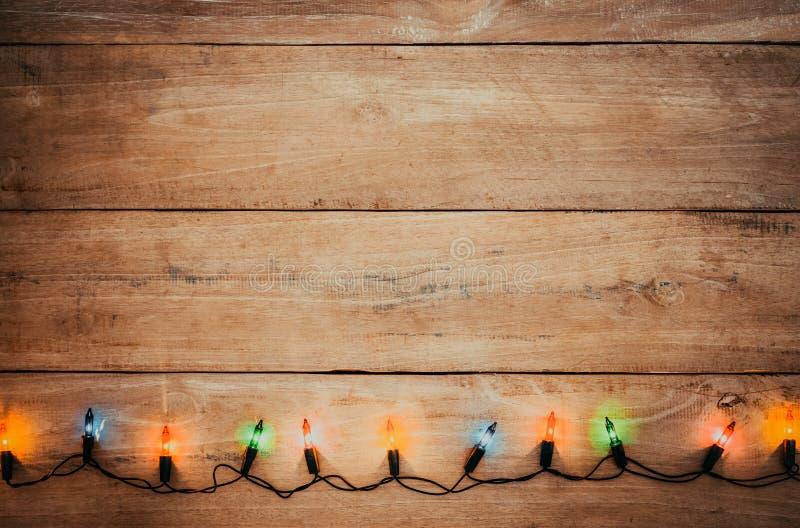 葡萄酒圣诞灯在老木头的电灯泡装饰 库存图片