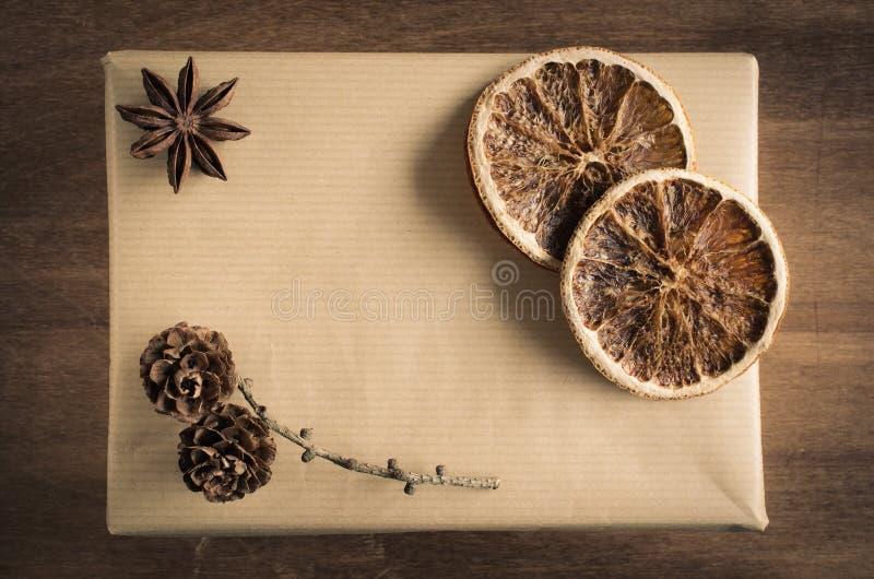 葡萄酒圣诞节卡拉服特用锥体、八角和干橙色切片在土气样式的礼物盒装饰的 库存图片