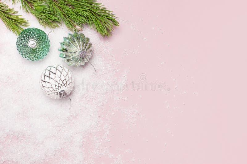 葡萄酒圣诞节在雪和杉木分支的新年球在桃红色背景平的被放置的拷贝空间 假日中看不中用的物品,美丽 免版税库存照片