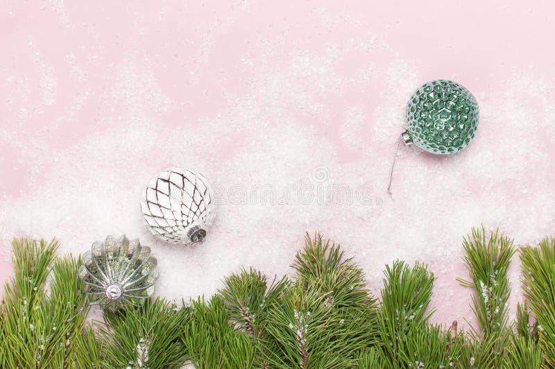 葡萄酒圣诞节在雪和杉木分支的新年球在桃红色背景平的被放置的拷贝空间 假日中看不中用的物品,美丽 图库摄影