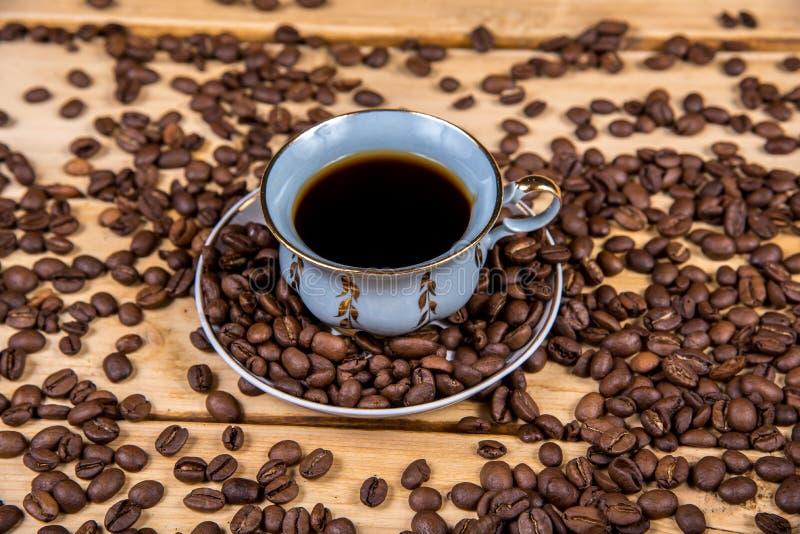 葡萄酒在一张木桌上的咖啡杯 免版税库存图片
