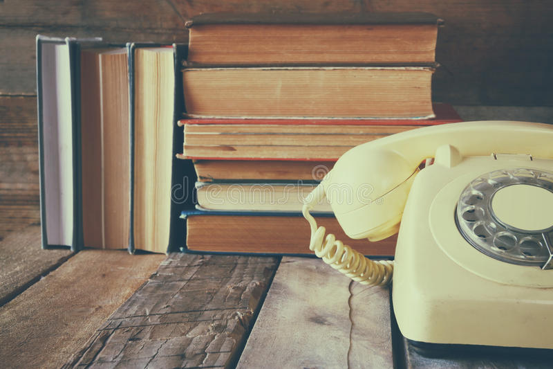 葡萄酒在堆的拨号电话在木桌的旧书旁边 库存照片