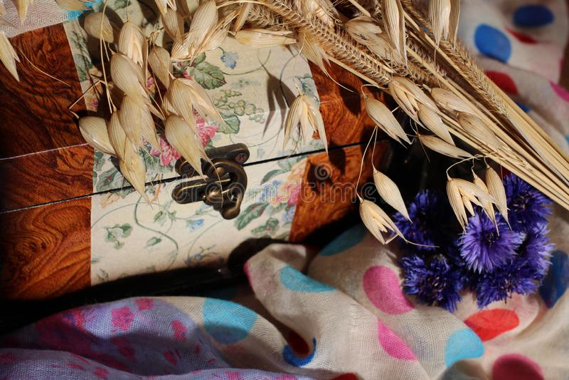 葡萄酒在多彩多姿的纺织品的葡萄酒箱子与花 库存照片