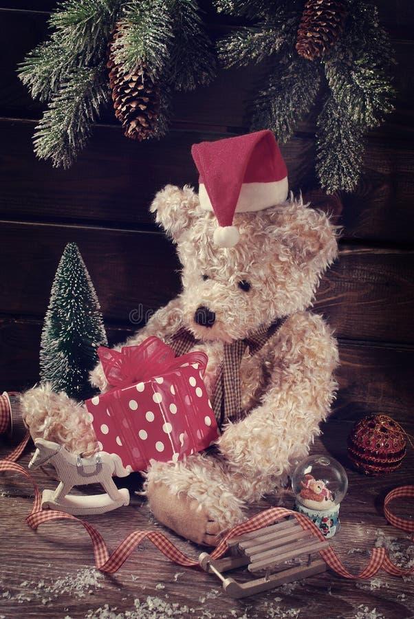 葡萄酒在拿着圣诞节礼物盒的圣诞老人帽子的玩具熊 库存照片