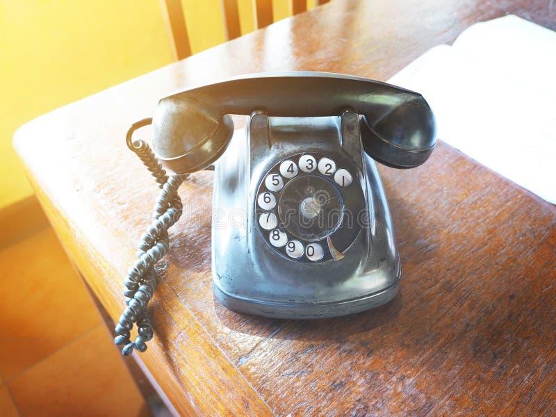 葡萄酒在木棕色桌上的拨号电话 库存图片